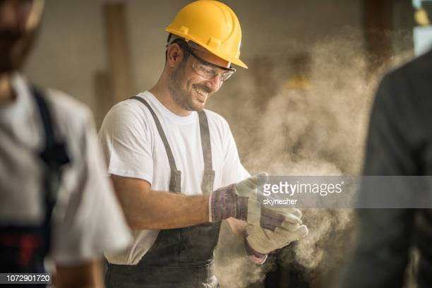 happy manual worker cleaning his gloves from sawdust at construction site. - building contractor stock pictures, royalty-free photos & images