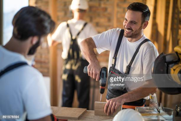 Happy manual worker talking to his colleague while working on home improvements.