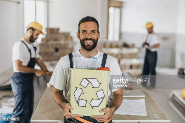 happy manual worker with recycle bin at construction site. - symbol stock pictures, royalty-free photos & images