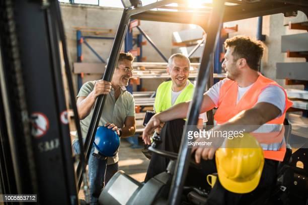 gelukkig arbeiders en hun manager praten op een pauze in een fabriek. - beschermende werkkleding stockfoto's en -beelden
