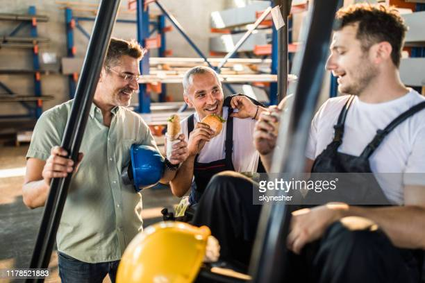 happy manual workers and their manager talking on a lunch break in a factory. - lunch break stock pictures, royalty-free photos & images