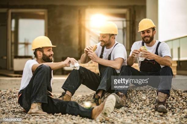glückliche arbeiter essen sandwiches auf eine mittagspause auf der terrasse. - pause machen stock-fotos und bilder
