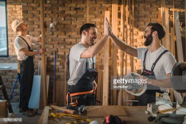 glückliche arbeiter geben einander hoch fünf auf baustelle. - handwerker stock-fotos und bilder