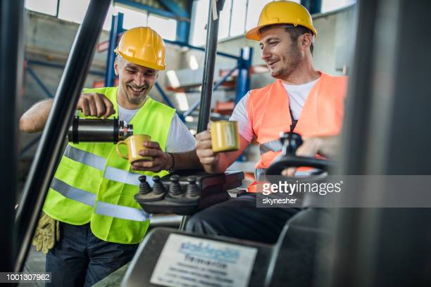 happy manual workers having a coffee break in industrial building. - resting stock pictures, royalty-free photos & images