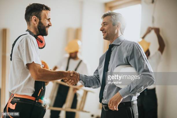 happy manual workers shaking hands with an architect at construction site. - inspector stock pictures, royalty-free photos & images