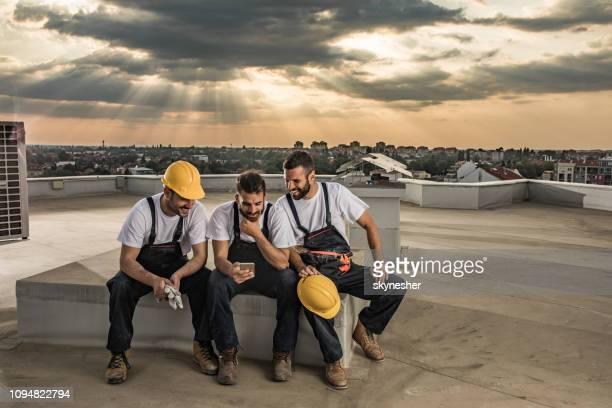 glückliche arbeiter mit handy auf einem dach nach der arbeit. - pause machen stock-fotos und bilder