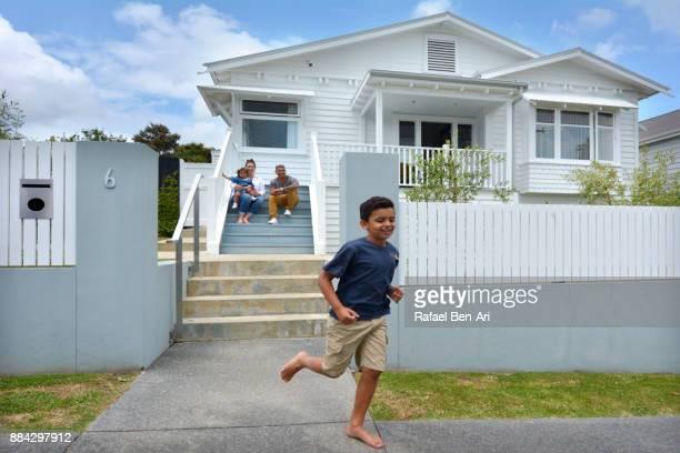 happy maori boy runs outside of his new home - rafael ben ari stock-fotos und bilder
