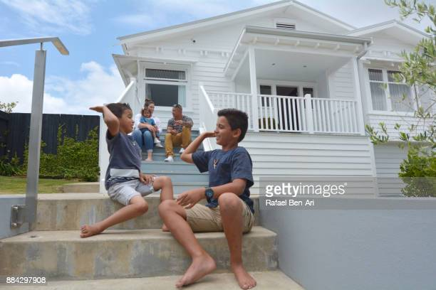 Happy Maori family sit on their new home stairs