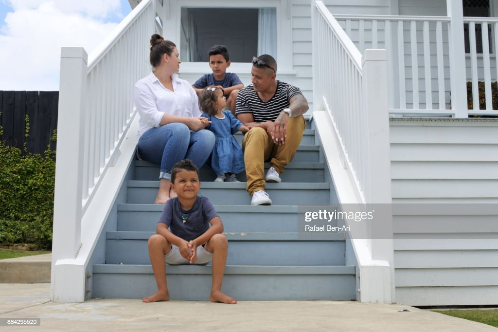 Happy Maori family sits on their new home stairs : Foto de stock