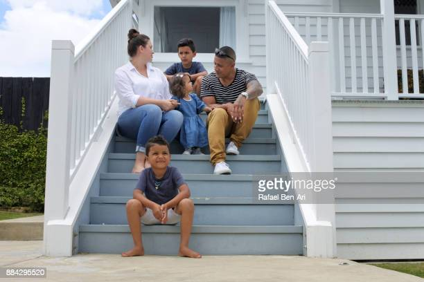 Happy Maori family sits on their new home stairs