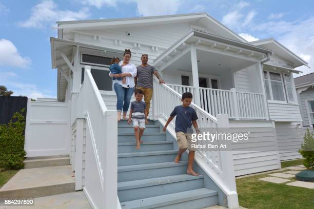Happy Maori family walk out of their new home