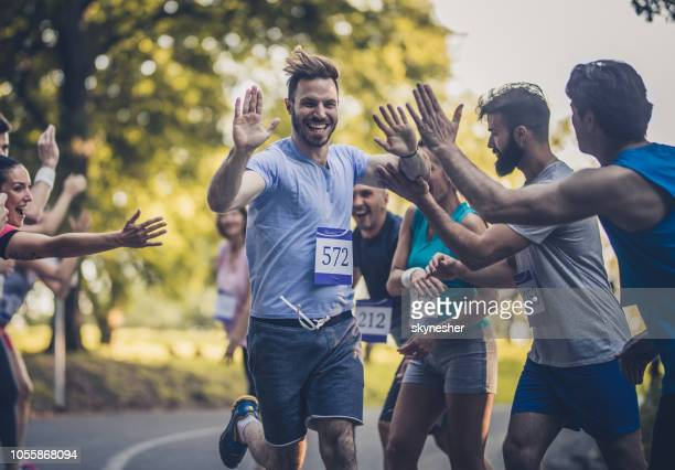 happy marathon runner greeting group of athletes at finish line. - finish line stock pictures, royalty-free photos & images