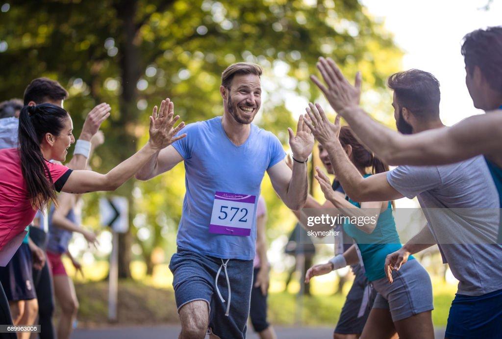 Happy marathon runner greeting group of athletes at finish line. : Stock Photo