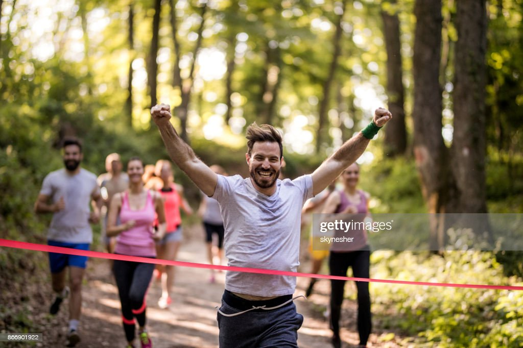 Happy marathon runner winning and crossing finish line with arms raised. : Stock Photo