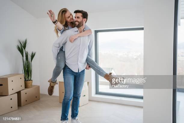 彼らの最初の家の購入を祝う幸せな夫婦 - 家の鍵 ストックフォトと画像