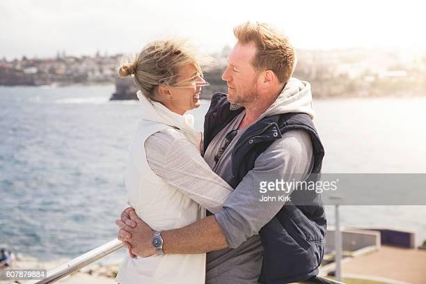 Happy mature adult couple embracing in warm coastal sun