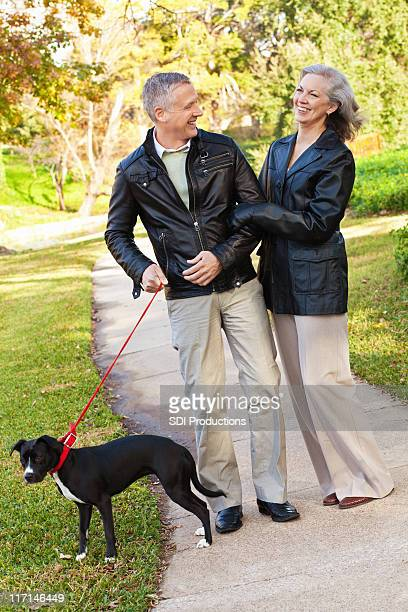 Happy Mature Adult Couple Laughing While Walking Dog at Park