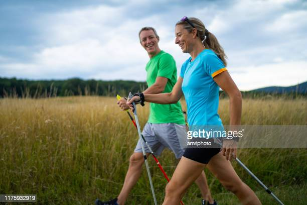 happy mature adult nordic walkers - hiking pole stock pictures, royalty-free photos & images