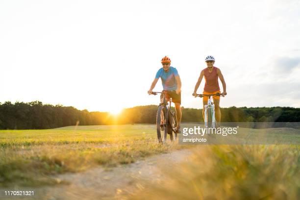 glücklich reife erwachsene sportliche paar auf mountainbikes in ländlichen landschaft bei sonnenuntergang - radfahren stock-fotos und bilder
