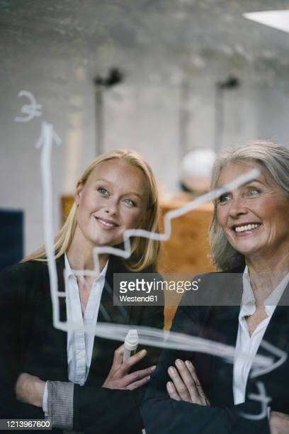 happy mature and young businesswoman looking at chart on glass pane in office - 後任 ストックフォトと画像
