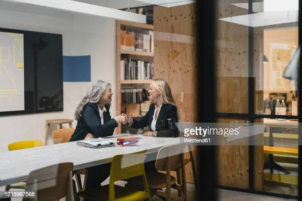 happy mature and young businesswoman shaking hands in loft office - 後任 ストックフォトと画像