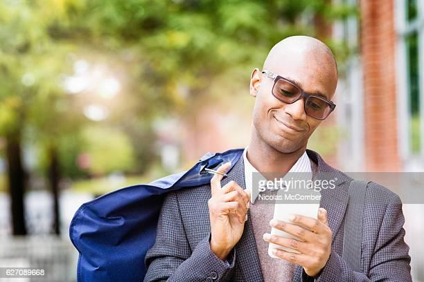 Happy mature black man smiling at text message horizontal