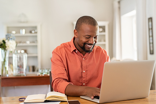 Happy mature black man using laptop 1152603283
