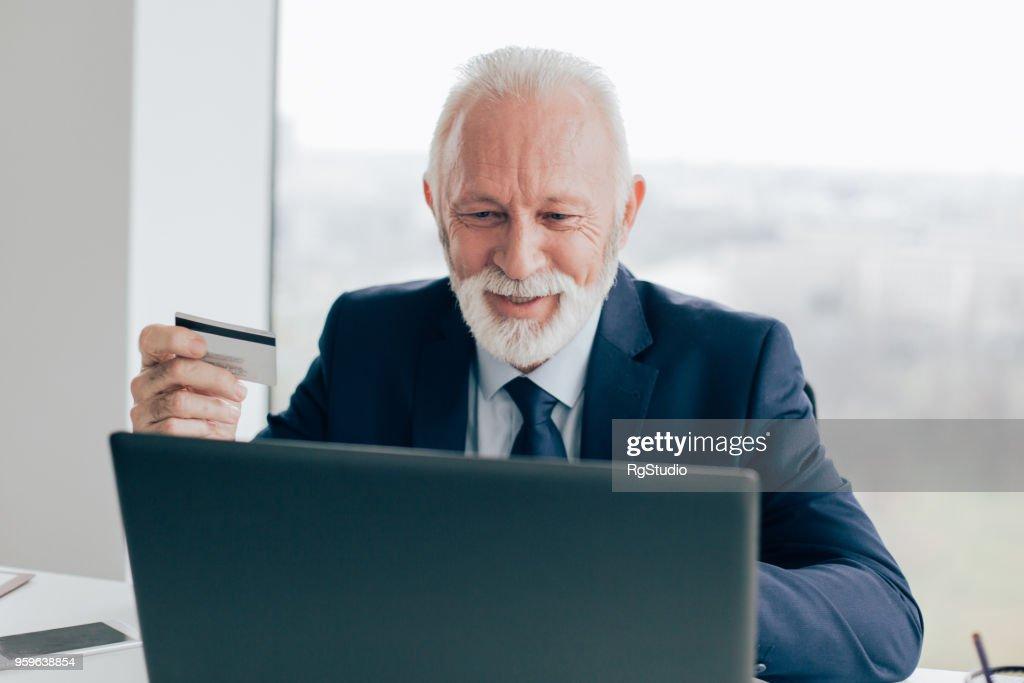 Glücklich ausgereifte Business-Mann mit Laptop und Holding-Kreditkarte : Stock-Foto