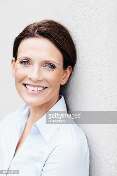 Happy mature business woman leaning against a wall