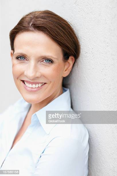 Happy mature business woman leaning on a wall