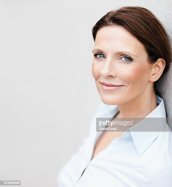 Happy mature business woman with copyspace leaning on a wall
