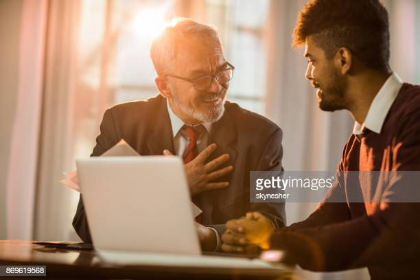 happy mature businessman communicating with his younger coworker in the office. - bank manager stock pictures, royalty-free photos & images