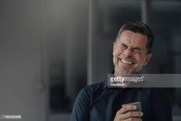 happy mature businessman holding a cup - lachen stock-fotos und bilder