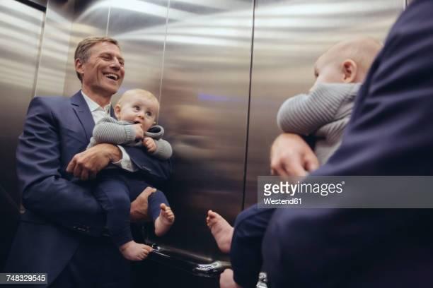 happy mature businessman holding baby boy looking in mirror in elevator - genderblend stockfoto's en -beelden