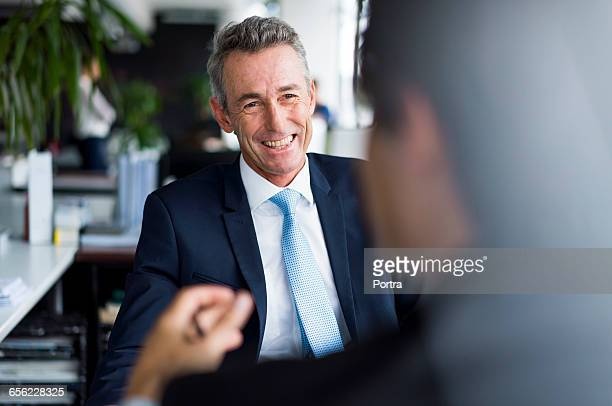 Happy mature businessman looking at colleague