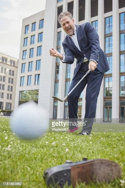 happy mature businessman playing golf on lawn in the city - golfschläger stock-fotos und bilder