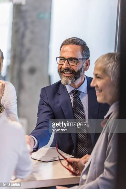 happy mature businessman shaking hands with his colleague on a meeting. - formal stock pictures, royalty-free photos & images