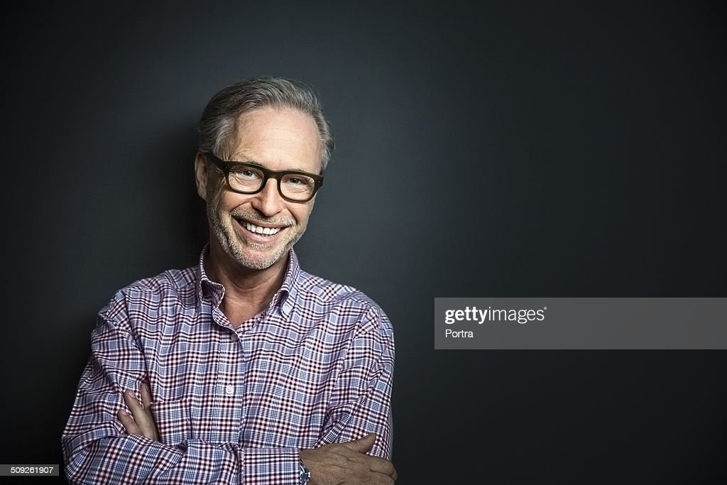 Happy mature businessman standing arms crossed : Stock Photo