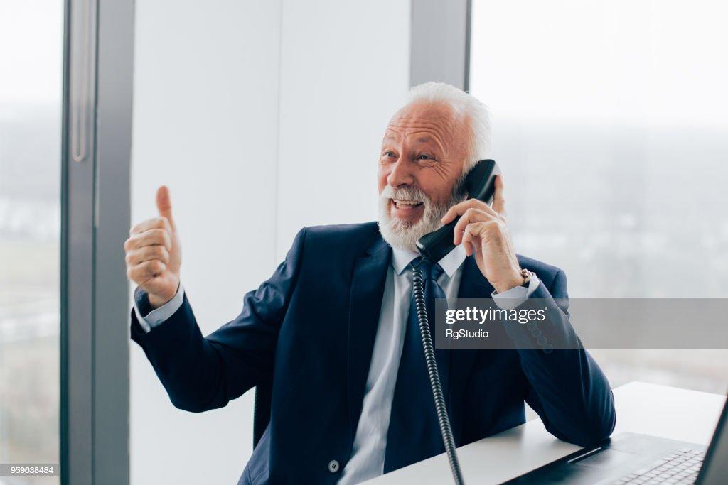 Glücklich reifer Geschäftsmann mit Handy und einen Daumen auftauchen : Stock-Foto