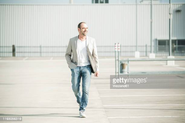 happy mature businessman walking on parking deck - white jacket stock pictures, royalty-free photos & images