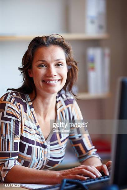 Happy mature businesswoman at office desk using computer