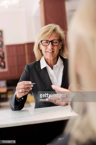 Happy mature businesswoman paying receptionist with credit card at hotel checkout