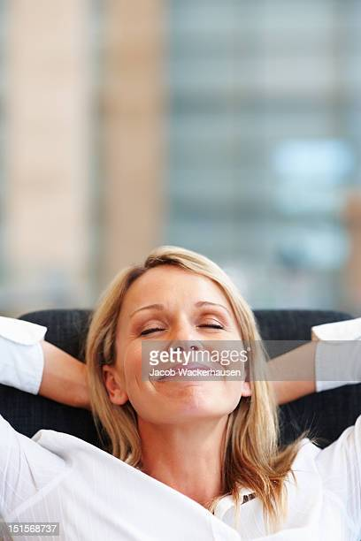 Happy mature businesswoman relaxing on chair