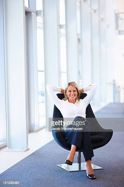 Happy mature businesswoman relaxing on office chair