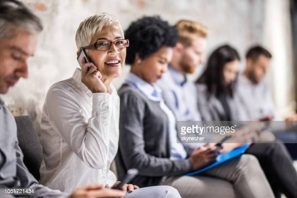 happy mature businesswoman talking on cell phone while waiting for job interview. - job search stock pictures, royalty-free photos & images