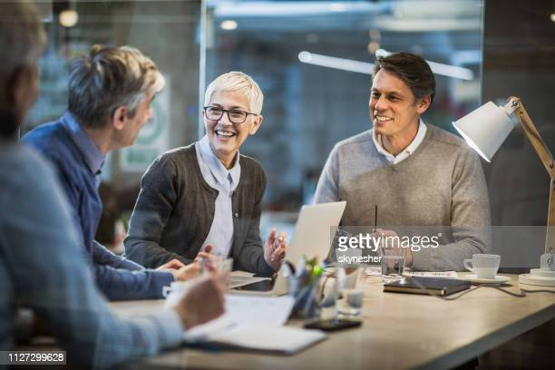 happy mature businesswoman talking to her colleagues on a meeting in the office. - white collar worker stock pictures, royalty-free photos & images