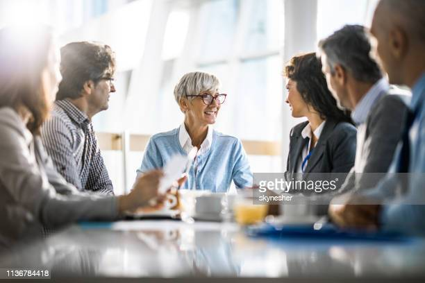 happy mature businesswoman talking to her colleagues on a meeting in the office. - businesswear stock pictures, royalty-free photos & images