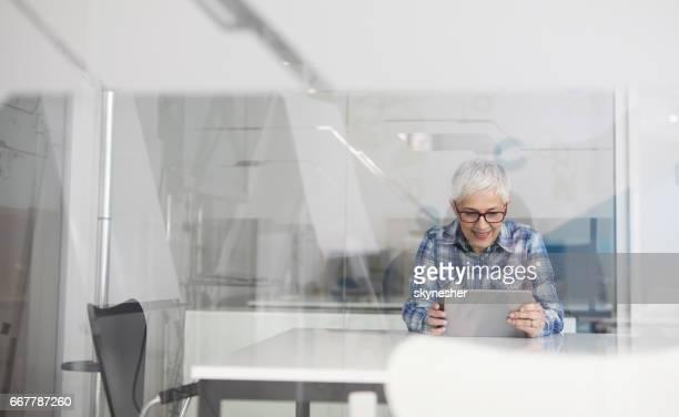 Heureuse femme mature à l'aide de tablette numérique dans son bureau.