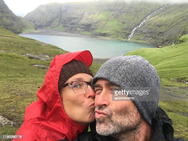 happy mature caucasian couple in the remote landscape of saksun, faroe islands - 40 49 years stock pictures, royalty-free photos & images