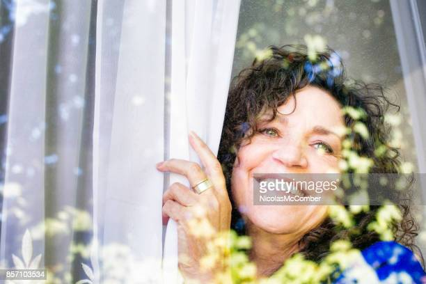 happy mature caucasian female looking  out of a window - menopause stock photos and pictures